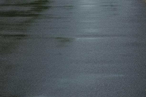 gri doku ıslak asfalt yolda - islak stok fotoğraflar ve resimler