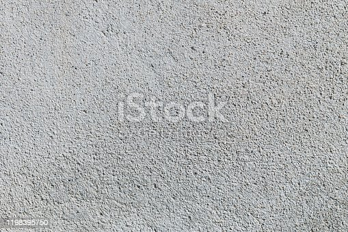 Gray textured cement wall background with fine concrete chips. Construction backgrounds.