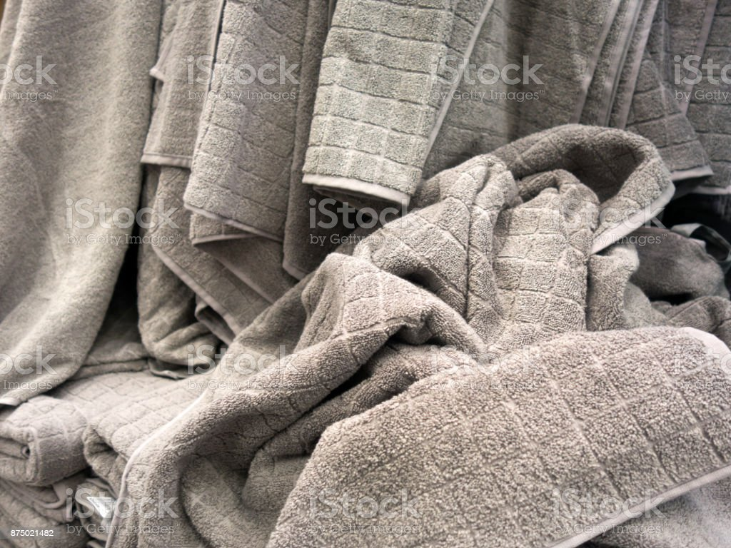 Gray towels hang on the hook in the bathroom stock photo