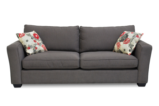 Two seat sofa / apartment sofa in grey upholstery accented with two pillows. Isolated on white.