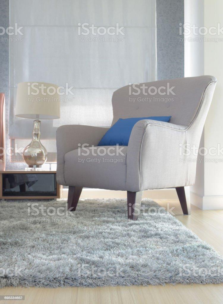 Graue Polster Sessel Mit Blauen Kissen Im Modernen Interieur