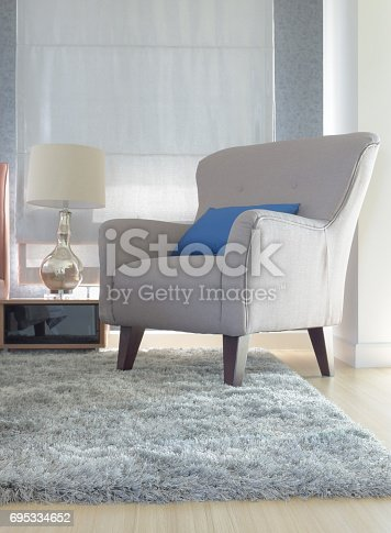 istock Gray upholstery armchair with blue pillow in modern interior living room 695334652
