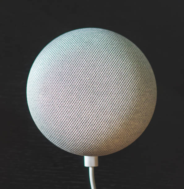 gray voice controlled mini smart speaker on black background gray voice controlled mini smart speaker on black background smart speaker stock pictures, royalty-free photos & images