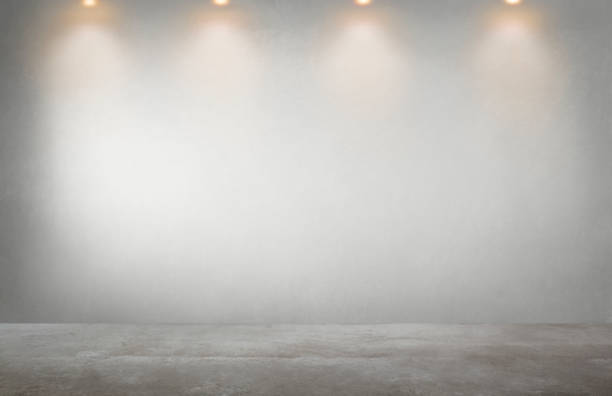 Gray wall with a row of spotlights in an empty room stock photo