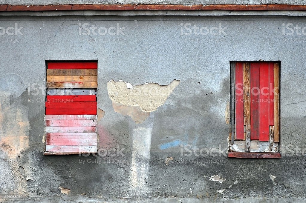 Gray wall with two boarded-up windows. royalty-free stock photo
