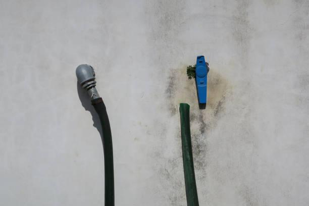 grijze muur met twee buizen en een blauwe kraan foto
