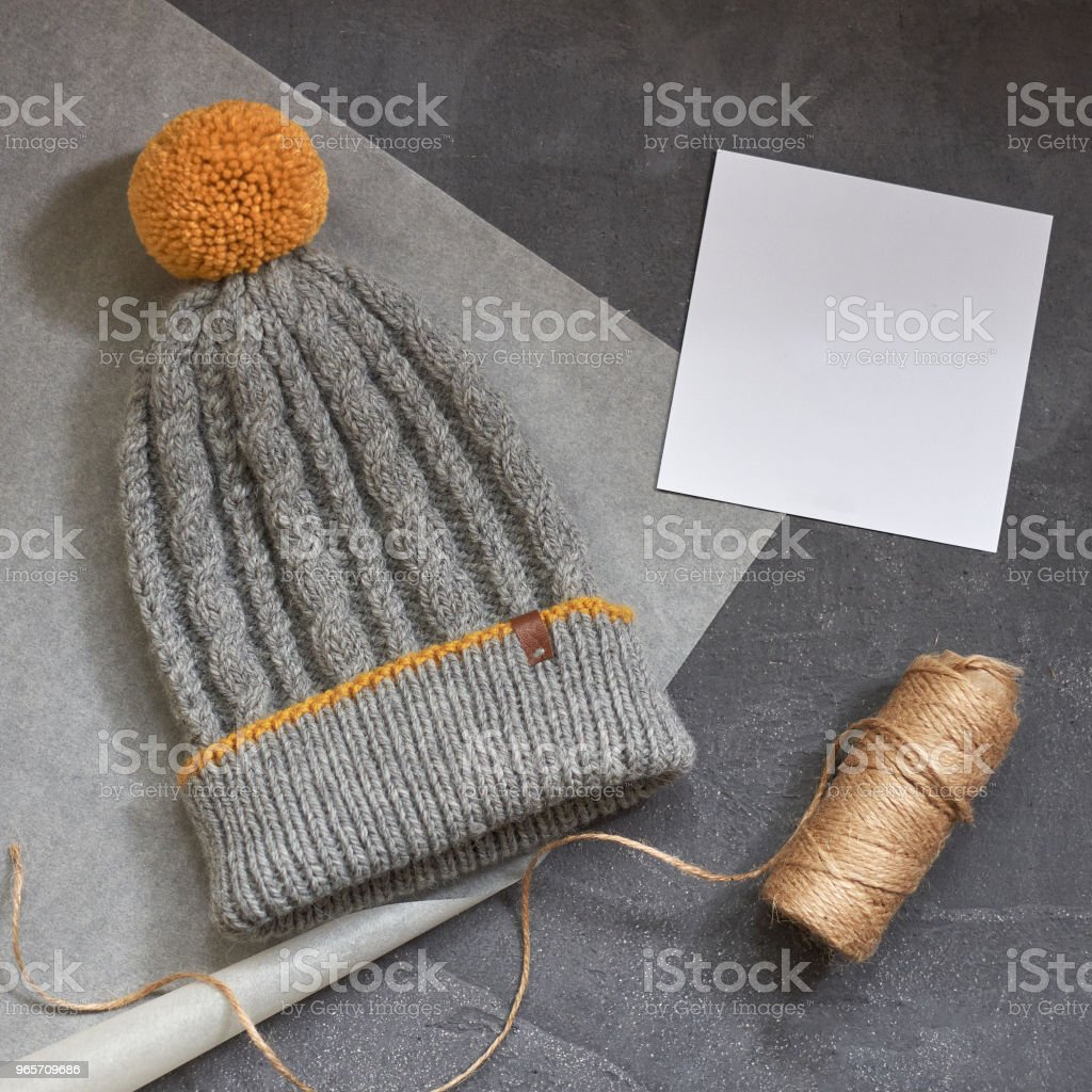 Gray winter hat with a jacquard pattern on a gray background - Royalty-free Autumn Stock Photo