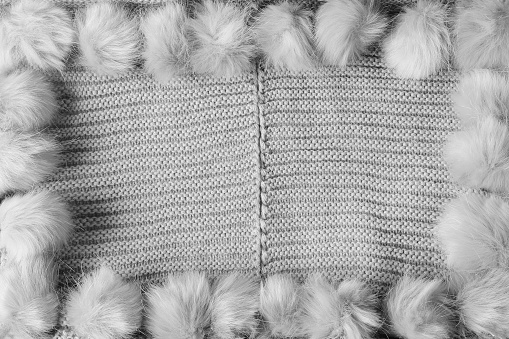 Gray winter textile background with copy space and a frame with fluffy tassels