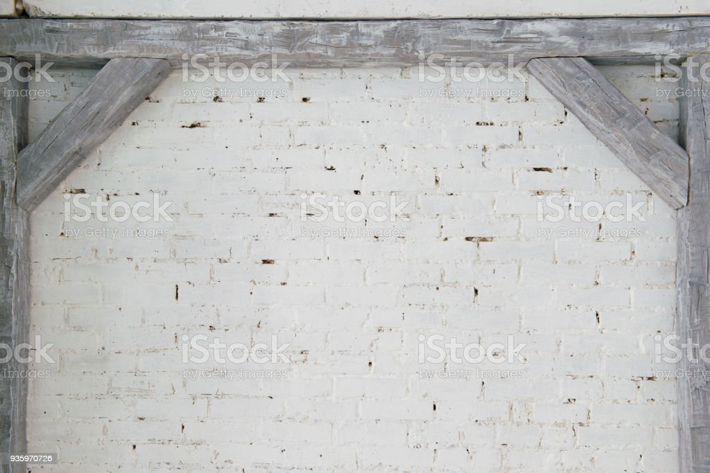 Gray wooden beams against a white brick wall стоковое фото