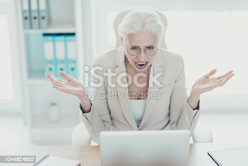 692461598 istock photo Gray-haired beautiful stylish mad crazy angry unhappy upset old lady wearing glasses, screaming, showing devastation, sitting in front of netbook at workplace workstation 1044824852