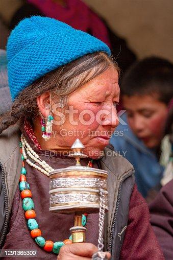 Lamayuru, India - June 17, 2012: Older gray-haired ladakhi women with hand prayer wheels in traditional clothes and jewelry prays with eyes closed among crowd of observers on buddhist Yuru Kabgyat festival performance in the Lamayuru monastery