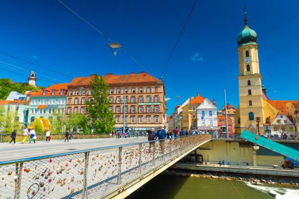 graz, österreich: blick auf die altstadt am sonnigen tag. franziskanerkirche und die historischen altbauten mit orangefarbenen dächern - stadt graz stock-fotos und bilder