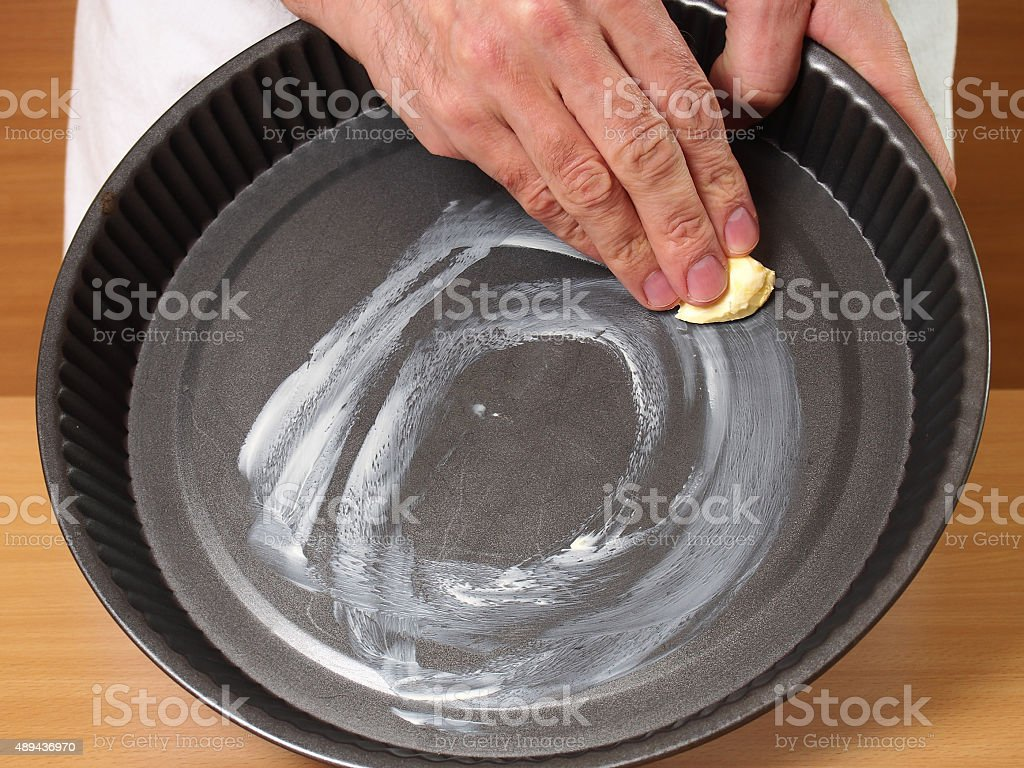 Grease pan with butter. Making Apple Pie Tart Series. stock photo