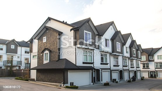 istock Great and comfortable neighborhood. A row of townhouses at the empty street. 1060816172