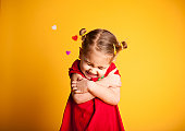 Color image of a little girl giving herself a big Valentine hug with hearts in the background on yellow.