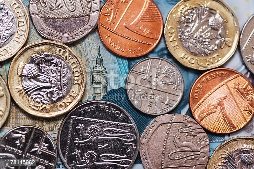 Diverse Great Britain Pound (GBP) coins. The Big Ben design in the background comes from a 5 GBP banknote.