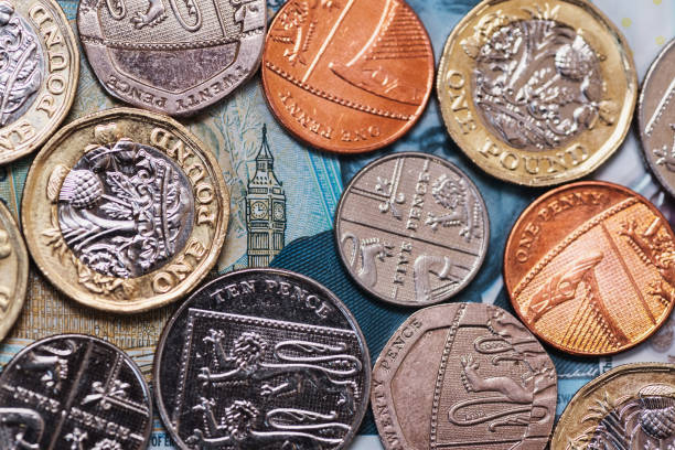 Great Britain Pound (GBP) coins and Big Ben from a 5 GBP banknote stock photo