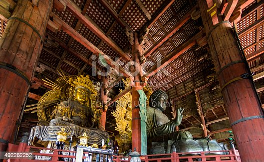 Nara, Japan - October 6, 2015: The Daibutsuden at Nara has the world's largest bronze statue of the Buddha and other two Bodhisattava (seen left).