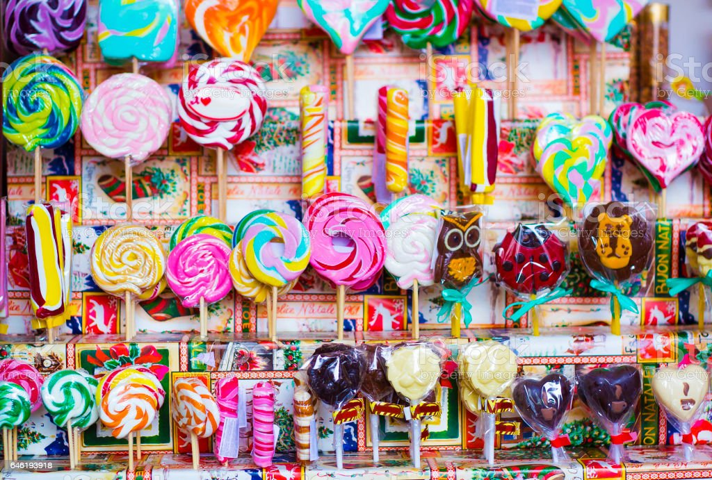 Great choice of colorful caramel on stick and chocolate candy for sale in shop window stock photo