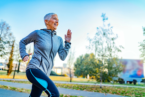 Joyful Senior Woman in Fitness Outfit Get Morning Running. Senior Woman Doing Her Jogging Outside at Public Park Trail. Mature Caucasian Woman Exercising at Park - Fitness, Sport, Training, Park and Lifestyle Concept.
