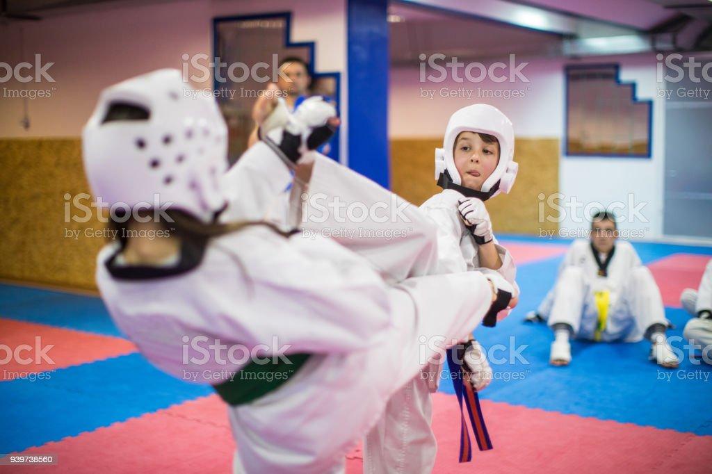 Boy and girl fighting in taekwondo indoors