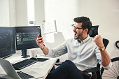 istock Great! Excited young trader or businessman in formalwear and eyeglasses shouting and gesturing in office while looking at trading charts on his smartphone 1147352176