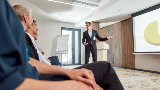 great expectations. full-length shot of young male speaker with headset in suit presenting a chart on the screen while giving a talk at business meeting, economic forum - theatre full of people stage foto e immagini stock