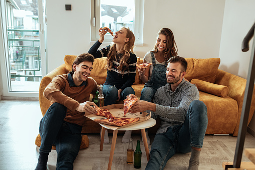 Friends sitting in the living room and eating pizza