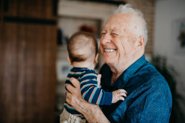 Great grandfather filled with joy embracing his great grandson Great grandfather filled with joy embracing his great grandson grandson stock pictures, royalty-free photos & images
