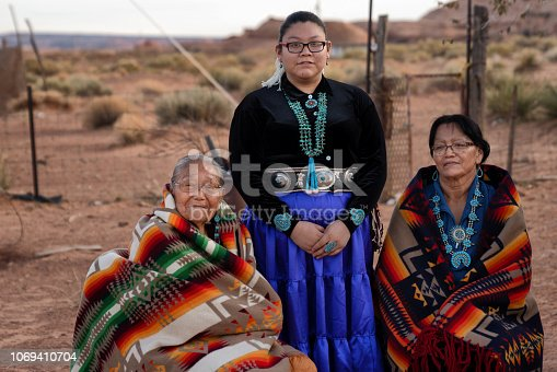 Three generation women, with two grandmothers and a granddaughter, all native American Navajo women sitting and posing in a group outside