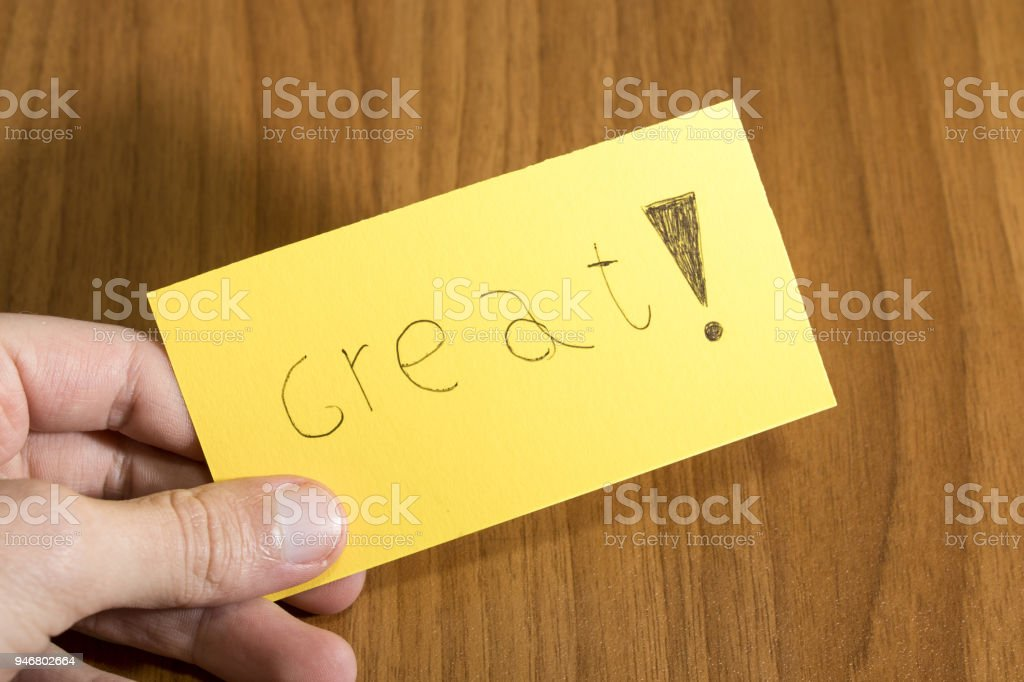 Great handwrite on a yellow paper with a pen on a table composition stock photo