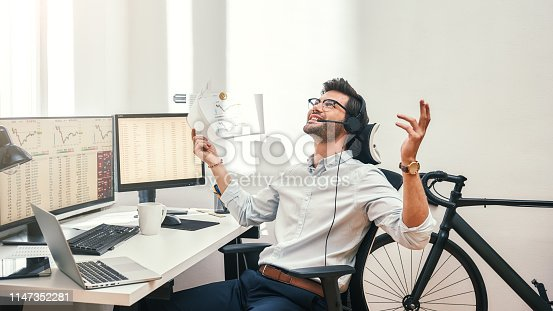Great! Happy and successful bearded trader in headset holding financial report, talking with client and gesturing while sitting in front of monitor screens in the office. Success concept. Trade concept. Call center
