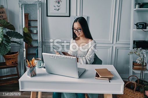 Beautiful young woman smiling and working using digital tablet while sitting in home office