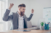 istock Great job! Very excited businessman is celebrating the growth of conmpany`s income. Hia hands are raised with fists. Victory! 941299766
