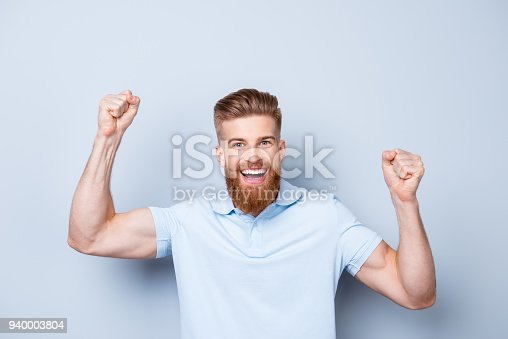 1092211952 istock photo Great job! Very excited young red bearded stylish freelancer is celebrating the growth of conmpany`s income. His hands are raised with fists. Victory! 940003804