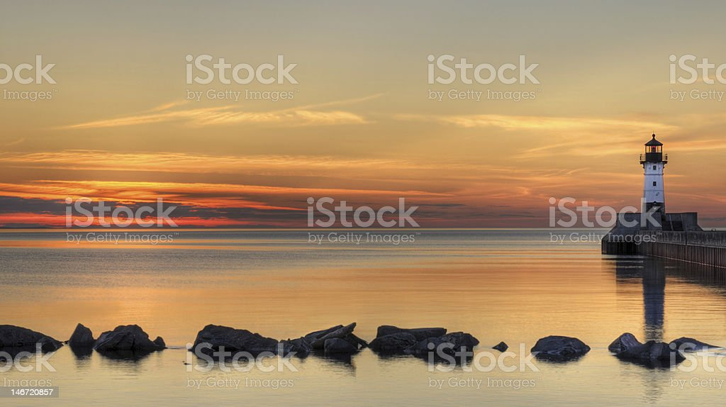 Great Lake Lighthouse Sunrise with Rocks stock photo