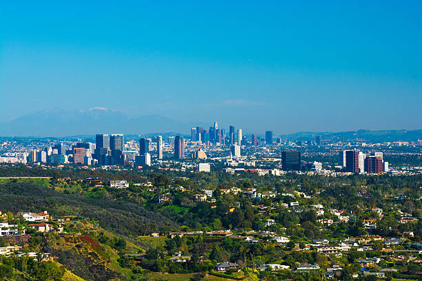 Great Los Angeles city aerial overview with Downtown and Westside Los Angeles city overview with houses on the foothills of Pacific Palisades and Brentwood in the foreground, West Los Angeles / Westside skylines of Century City, Westwood, and Brentwood midway, and Downtown Los Angeles and Mount Baldy and the San Gabriel Mountains in the background. westwood neighborhood los angeles stock pictures, royalty-free photos & images