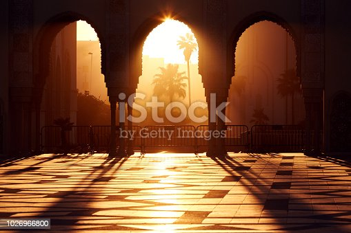 istock Great mosque of Hassan 2 at sunset in Casablanca, Morocco. Beautiful Arches of the Arab mosque in the sunset, sunlight rays 1026966800