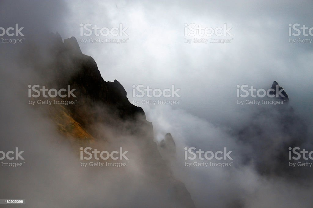 Great mountains disappearing under the strong fogs stock photo
