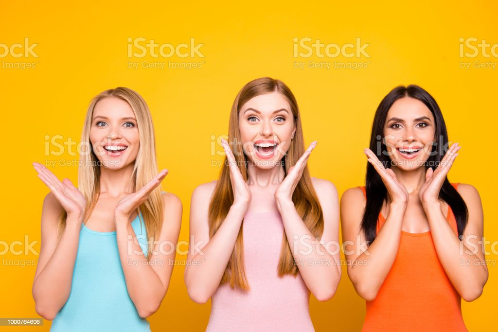Great! Portrait of amazed pleased trio holding palms near face having...