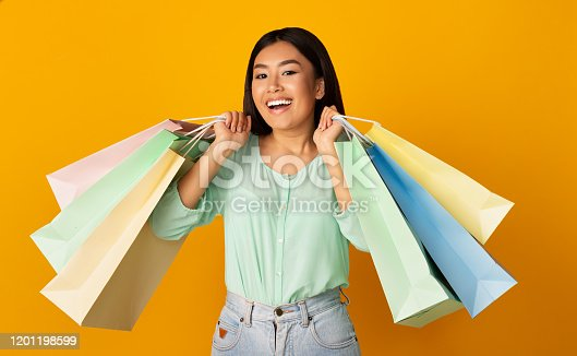 Great shopping. Asian girl holding colourful paper bags on yellow studio background