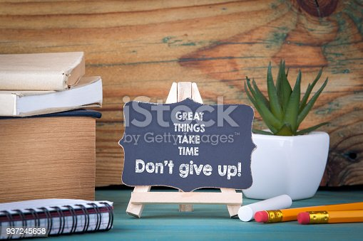Great things take time Don't give up. small wooden board with chalk on the table