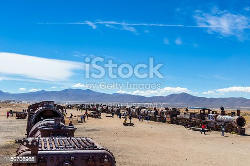 Train cemetery, Uyuni, Bolivia – April, 2019 : Abandoned old steam locomotives, vintage trains lie on the white ground and some tourist visiting a popular, minor attraction nearby Salar de Uyuni