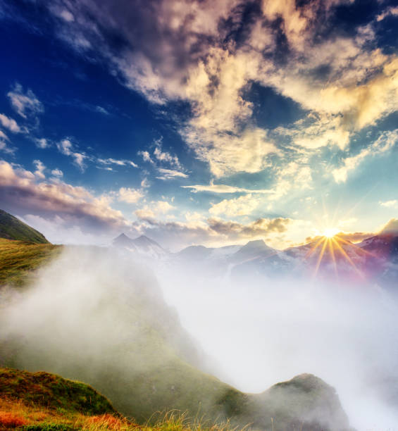 A great view of the foggy hills and cloudy sky which glowing by sunlight.
