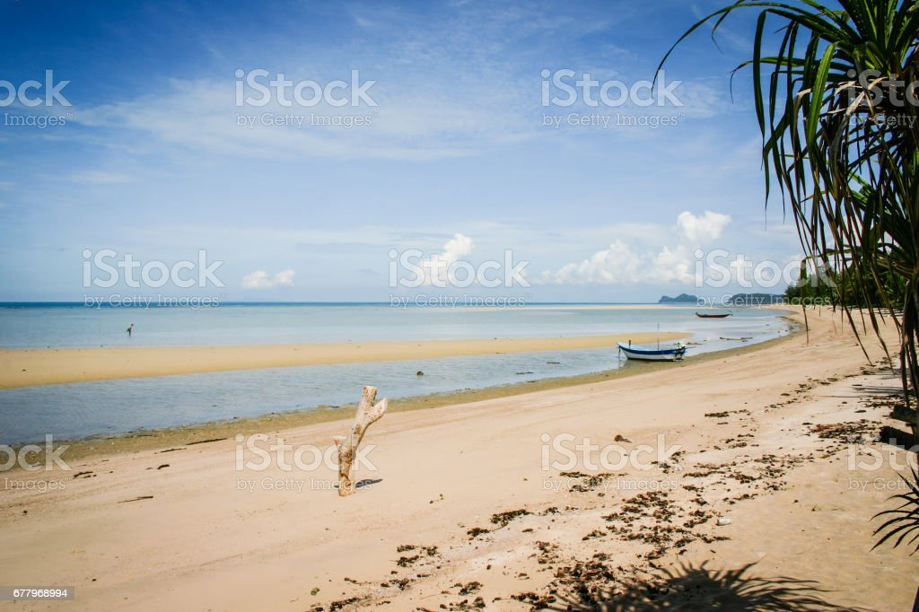 Great view over the sandy beach. Beautiful clouds in the blue sky. Islands at the horizont. Some palms. Boat in water. royalty-free stock photo