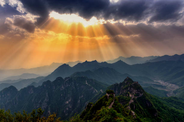 Great Wall and Opening Skies A dramatic sky with the sun breaking through the clouds in the Great Wall of China. emergence stock pictures, royalty-free photos & images