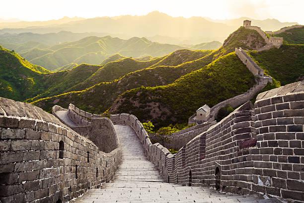 great wall unter der sonne bei sonnenuntergang - chinesische mauer stock-fotos und bilder
