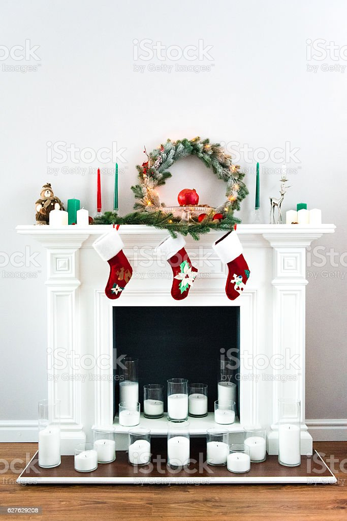 great white fireplace decorated with many candles stock photo