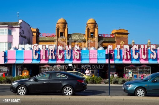 Great Yarmouth, England - September 28, 2011: Holiday-makers stroll along Marine Parade, Great Yarmouth, Norfolk, in the late September sunshine, outside an amusement arcade with circus signs. The Hippodrome Circus is the only surviving dedicated circus building in the UK and dates from 1903. The circus runs for two months every summer holiday season, attracting international acts. An unusual feature is its aquatic event, with synchronised swimmers, at the end of each circus show. The building, which is like a miniature Albert Hall inside, stages many other events out-of-season.