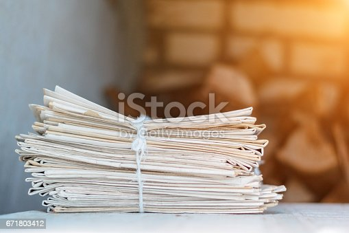 istock Greater pack of newspapers on a table with a rope 671803412